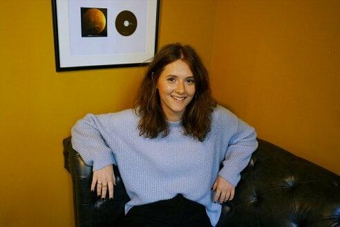 Frau auf Sofa vor einer gelben Wand